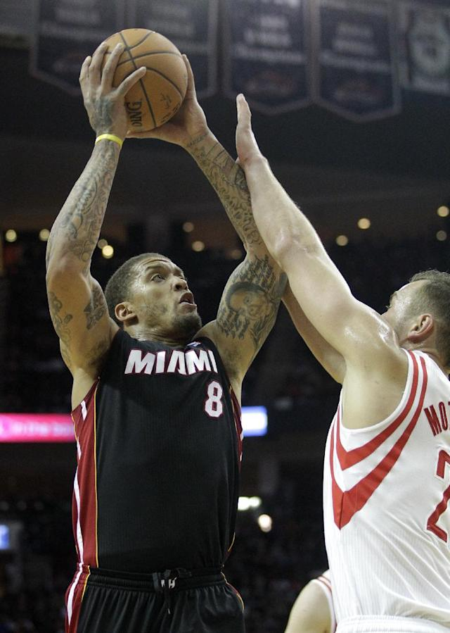 Miami Heat forward Michael Beasely (8) takes a shot over Houston Rockets forward Donatas Motiejunas (8) during the first half of an NBA basketball game, Tuesday, March, 4, 2014, in Houston. (AP Photo/Patric Schneider)