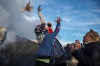 Worshippers throw their offerings into the volcano of Mount Bromo as a sacrifice to the gods