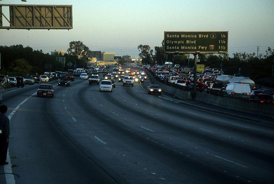 Police cars pursue the Ford Bronco driven by Al Cowlings, carrying fugitive murder suspect O.J. Simpson, on a 90-minute slow-speed car chase June 17, 1994 on the 405 freeway in Los Angeles. (Getty)