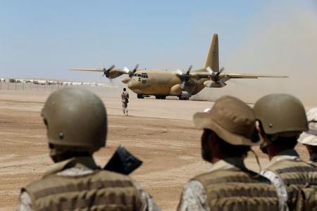 Saudi soldiers watch as a Saudi military cargo plane lands to deliver aid at an airfield in Marib, Yemen January 26, 2018. Picture taken January 26, 2018. Picture taken January 26, 2018. REUTERS/Faisal Al Nasser
