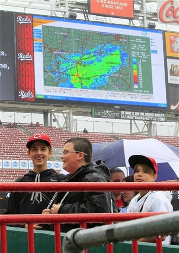 Fans stand near the dugout while the scoreboard displays a weather radar map during a rain delay before a baseball game between the Washington Nationals and the Cincinnati Reds, Sunday, May 13, 2012, in Cincinnati. (AP Photo/Al Behrman)