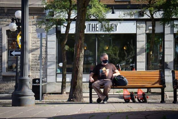 A man in a mask sits on a bench in Ottawa's ByWard Market last week. (Trevor Pritchard/CBC - image credit)