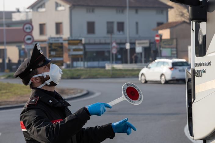 GUARDAMIGLIO, ITALY - FEBRUARY 24: An Italian Carabinieri officer, wearing a respiratory mask, talks to a truck driver (not in the picture) at a road block on February 24, 2020 in Guardamiglio, south-west Milan, Italy. Guardamiglio is a town nearby one of the ten small towns placed under lockdown after coronavirus sparked infections throughout the Lombardy region. Italy is the last country to be hit hard by the virus with 6 dead and more than 229 infected as of today. The spread marks Europe's biggest outbreak, prompting Italian Government to issue draconian safety measures. (Photo by Emanuele Cremaschi/Getty Images)