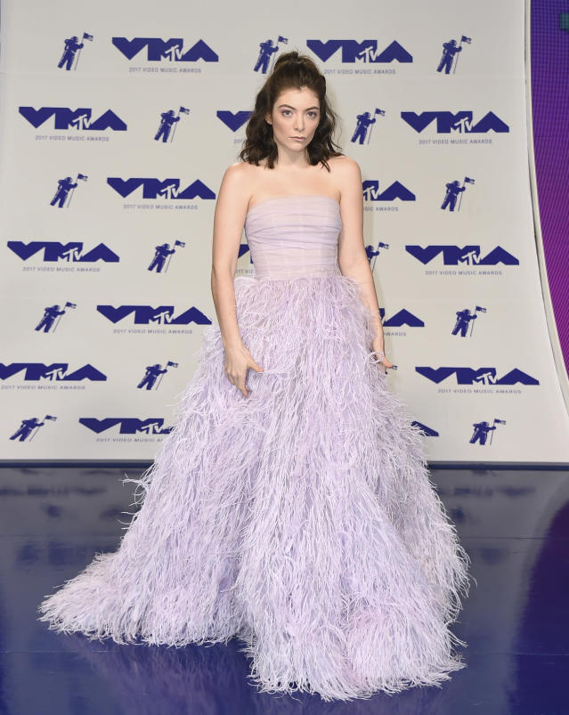 <p>Lorde had a total princess moment in a lilac gown with a strapless bodice and feather skirt. With the fancy dress, she kept her hair casual with a half-up, half-down topknot. (Photo: AP) </p>