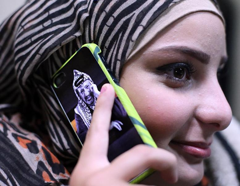 A Palestinian woman uses a mobile phone bearing a portrait of late Palestinian leader Yasser Arafat on November 5, 2014, in the West Bank city of Ramallah (AFP Photo/Abbas Momani)