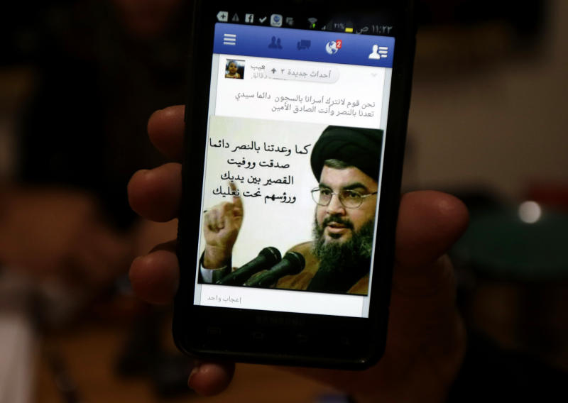 "A relative of one of nine Lebanese Shiite pilgrims, who were kidnapped by a rebel faction in northern Syria in May 2012, holds her mobile phone as she shows a portrait of Hezbollah leader Sheik Hassan Nasrallah on her Facebook page, in the southern suburb of Beirut, Lebanon, Saturday, Oct. 19, 2013. Nine Shiite pilgrims from Lebanon kidnapped in Syria were freed late Friday night as part of a negotiated hostage deal that could see two Turkish pilots held by Lebanese militants released, officials said. The complicated three-way deal also potentially includes the release of female prisoners now held by the embattled government of Syrian President Bashar Assad. Arabic writing on the mobile screen reads, ""We are people who don't leave their prisoners in jails. Always, our master, you promise us victory and you are truthful, as you always promised us with victory, you were truthful, Qusair (a Syrian city) is in your hands and their heads under your shoes."" (AP Photo/Hussein Malla)"