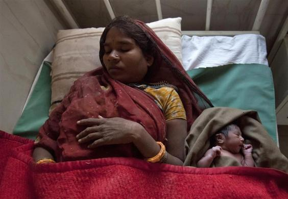 Anguri, a 26-year-old pregnant woman who just gave birth, rests on a bed along with her newborn baby in the post delivery ward at a community health centre in the remote village of Chharchh, in the central Indian state of Madhya Pradesh, February 24, 2012.