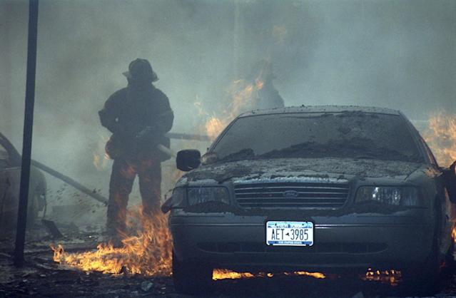 A fireman battles to put out the flames tearing through a nearby vehicle. (Caters)