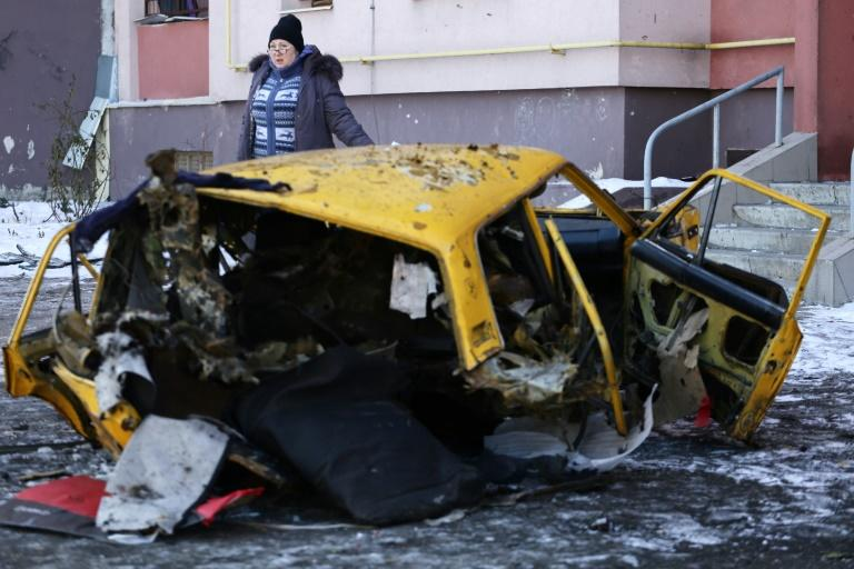 A woman walks past a destroyed car in Donetsk on February 9, 2017. Ukraine's case in The Hague accuses Russia of breaking a treaty by supporting pro-Russia rebels