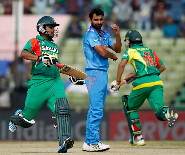 Bangladesh's Shamsur Rahman (L) and Anamul Haque run between the wickets as India's bowler Mohammed Shami (C) watches during their Asia Cup 2014 one-day international (ODI) cricket match in Fatullah February 26, 2014. REUTERS/Andrew Biraj (BANGLADESH - Tags: SPORT CRICKET)
