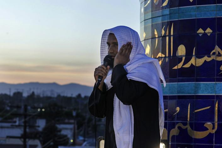 """Mahmood Nadvi uses a handheld microphone to share the adhan, the Islamic call to prayer, at King Fahad Mosque in Culver City. <span class=""""copyright"""">(Irfan Khan / Los Angeles Times)</span>"""