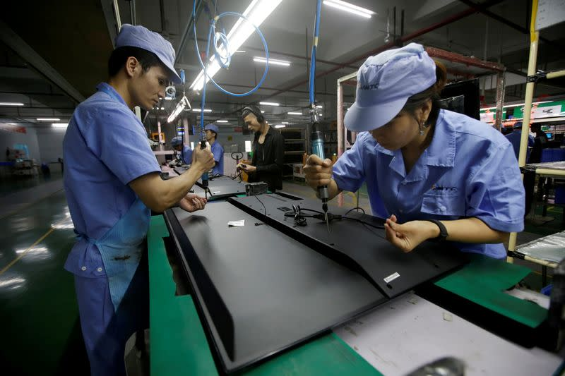 FILE PHOTO: Employees work on the production line of a television factory under Zhaochi Group in Shenzhen