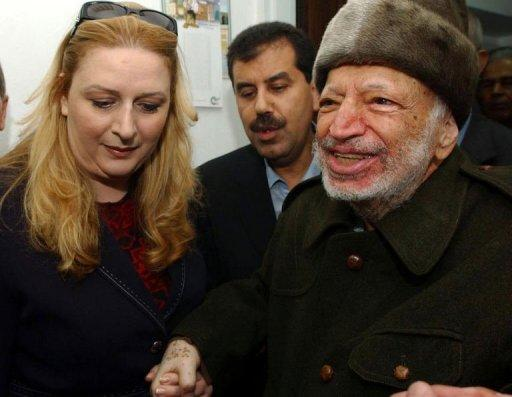 Ailing Palestinian leader Yasser Arafat (R) is assisted by his wife Suha (L) as he leaves his West Bank headquarters in Ramallah in 2004, in this photo provided by the Palestinian President Office. One of the Middle East's greatest political mysteries will come a step closer to being solved on Tuesday when scientists exhume Arafat's remains to see if he was poisoned