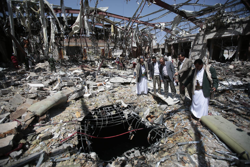 FILE - In this Oct. 13, 2016, file photo, members of the Higher Council for Civilian Community Organization inspect a destroyed funeral hall as they protest against a deadly Saudi-led airstrike on a funeral hall in Sanaa, Yemen. President Joe Biden's announcement that the U.S. will end its support of a Saudi-led coalition's years-long war against Yemen's Houthi rebels likely will increase pressure on the kingdom to end its campaign there, though reaching an enduring peace for the Arab world's poorest country still remains in question. (AP Photo/Hani Mohammed, File)