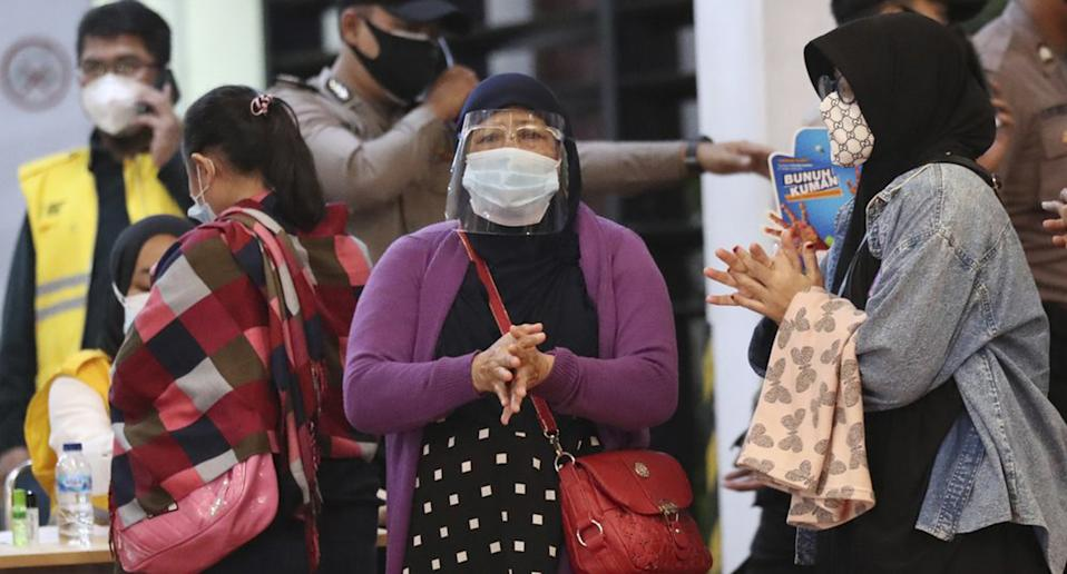 Relatives of passengers arrive at a crisis center set up following a report that a Sriwijaya Air passenger jet has lost contact with air traffic controllers shortly after take off, at Soekarno-Hatta International Airport in Tangerang, Indonesia,Saturday, Jan. 9, 2021. The Boeing 737-500 took off from Jakarta and lost contact with the control tower a few moments later.
