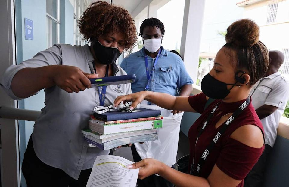 Teacher Michaelle Joseph, left, gives books and iPads to Louna Dorcelien, right, at St. Mary's Cathedral School on Wednesday, August 19, 2020 in Miami's Little Haiti neighborhood. Teacher Jeffrey Phillipe, center, waits to place the items in a bag. The supply distribution event was to help prepare students for the first day of online learning.