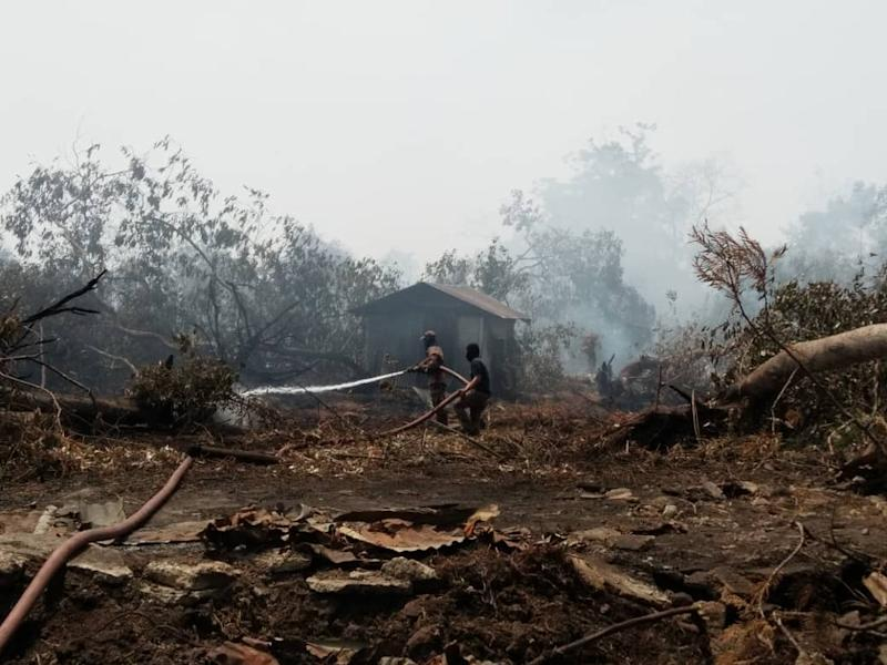Firemen containing the secondary forest fire at Jalan Tanjung Kupang in Kampung Pekajang, Gelang Patah today. — Picture courtesy of the Johor Fire and Rescue Department