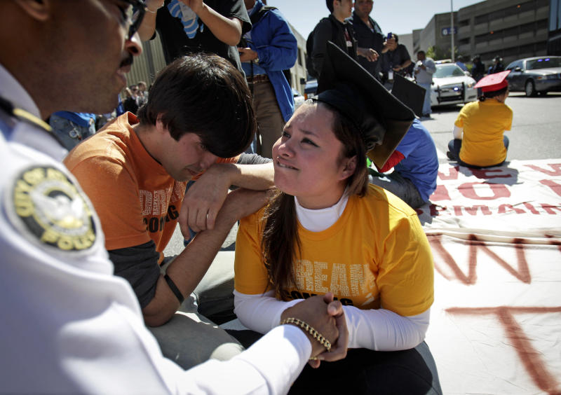 FILE - In this April 5, 2011 file photo, illegal immigrant Viridiana Martinez, right, is comforted by activist Mohammad Abdollahi, as Maj. K.E. Williams, left, of the Atlanta Police Department, warns her of arrest unless she moves while protesting for rights for higher education for illegal immigrants in Atlanta. A policy shift announced by President Barack Obama in June essentially gives certain young people brought to this country illegally immunity from deportation for at least two years and the chance to apply for a work permit. Now Martinez, Abdollahi and young activist leaders are deciding whether it's worth accepting a deal that falls far short of their demands. (AP Photo/David Goldman, File)