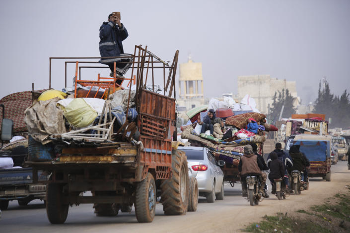 File - In this Monday, Jan. 27, 2020 file photo, Syrian refugees head northwest through the town of Hazano in Idlib province as the flee renewed fighting. Syrians are marking 10 years since peaceful protests against President Bashar Assad's government erupted in March 2011, touching off a popular uprising that quickly turned into a full-blown civil war. (AP Photo/Ghaith Alsayed, File)