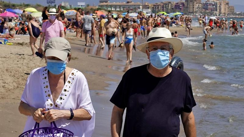 A couple wearing face masks on a beach in Valencia