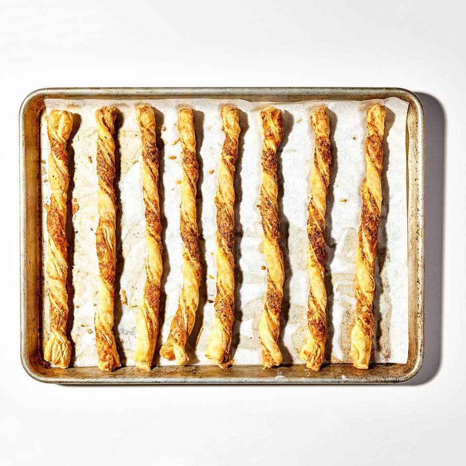 """Store-bought puff pastry is the MVP of party appetizers, and it has no higher calling than these crispy, buttery cheese straws. This flaky pre-made dough comes frozen, and it's best to let it thaw slowly overnight in the refrigerator to prevent splitting and cracking when rolling out. <a href=""""https://www.bonappetit.com/recipe/crispy-cheese-twists?mbid=synd_yahoo_rss"""">See recipe.</a>"""