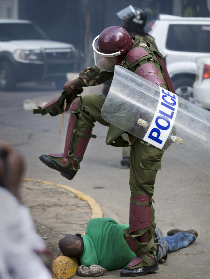A Kenyan riot policeman prepares to kick a protester as he lies in the street after tripping over while trying to flee from officers during a protest in downtown Nairobi, Kenya, May 16, 2016. Kenyan police have tear-gassed and beaten opposition supporters during a protest demanding the disbandment of the electoral authority over alleged bias and corruption. (AP Photo/Ben Curtis)