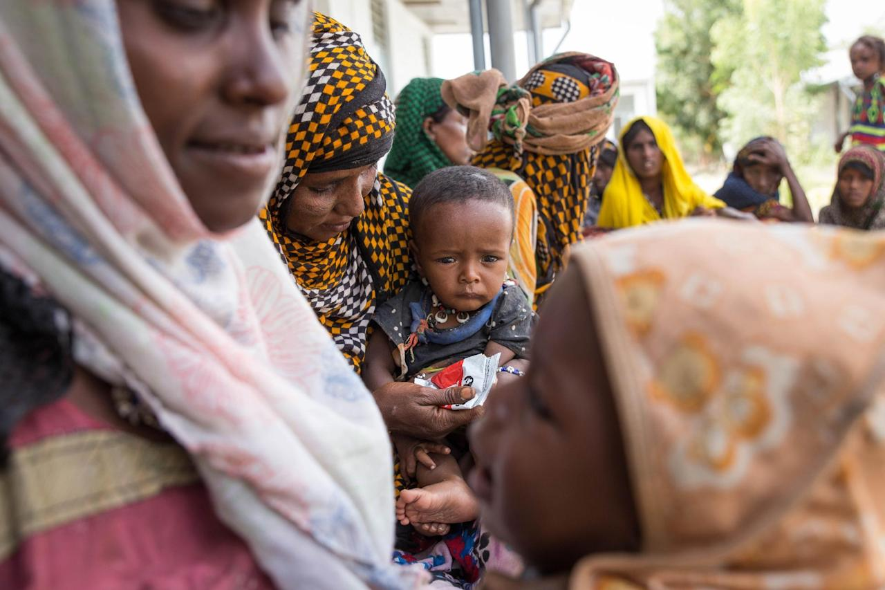 In this photo taken on Tuesday, Jan. 26, 2016, women wait to get their children examined, at Megenta Kebele clinic in a rural village Dubti Woreda, Afar, Ethiopia. Morbid thoughts linger on people's minds in the area. The crops have failed and farm animals have been dying amid severe drought that has left Ethiopia appealing for international help to feed its people. (AP Photo/Mulugeta Ayene)