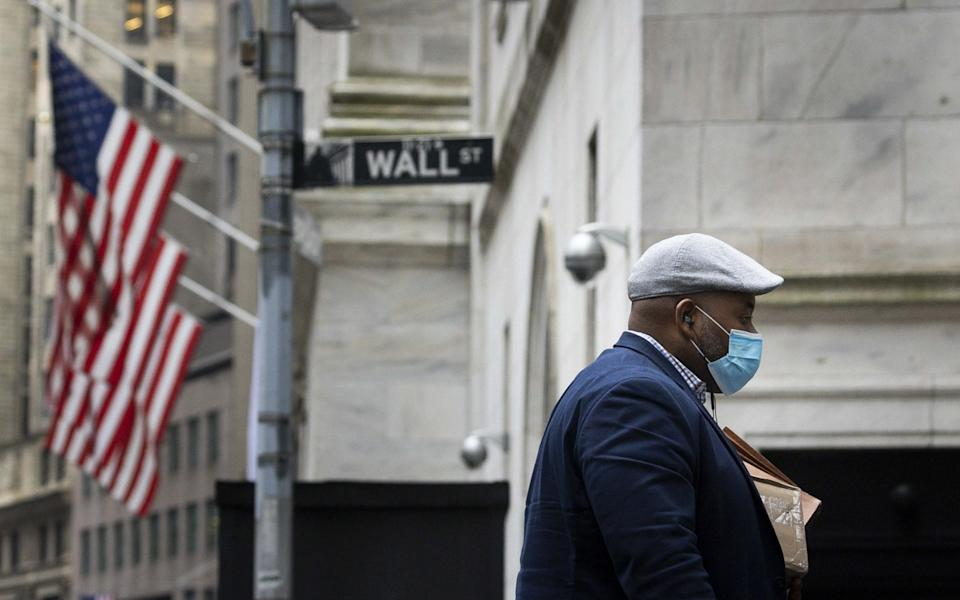 A man walks past the New York Stock Exchange on Wall Street in New York - JUSTIN LANE/EPA-EFE/Shutterstock