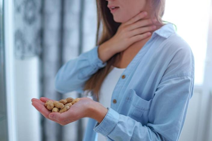 woman suffers from choking and cough from allergic reaction to peanut. Danger of nuts and food allergy