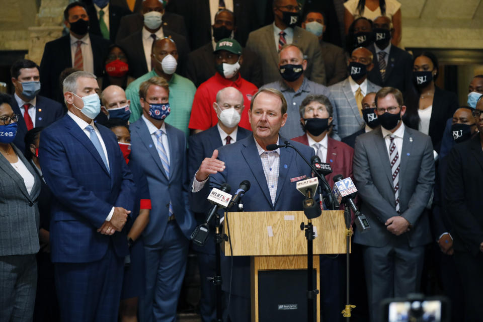 Mississippi basketball coach, Kermit Davis, center, joins other athletic staff from the state's public universities calling for a change in the Mississippi state flag, during a joint news conference at the Capitol in Jackson, Mississippi, on Thursday. Several head coaches met with both Lt. Gov. Delbert Hosemann and Speaker Philip Gunn in addition to their lawmakers, to lobby for the change by their respective bodies. (AP Photo/Rogelio V. Solis)