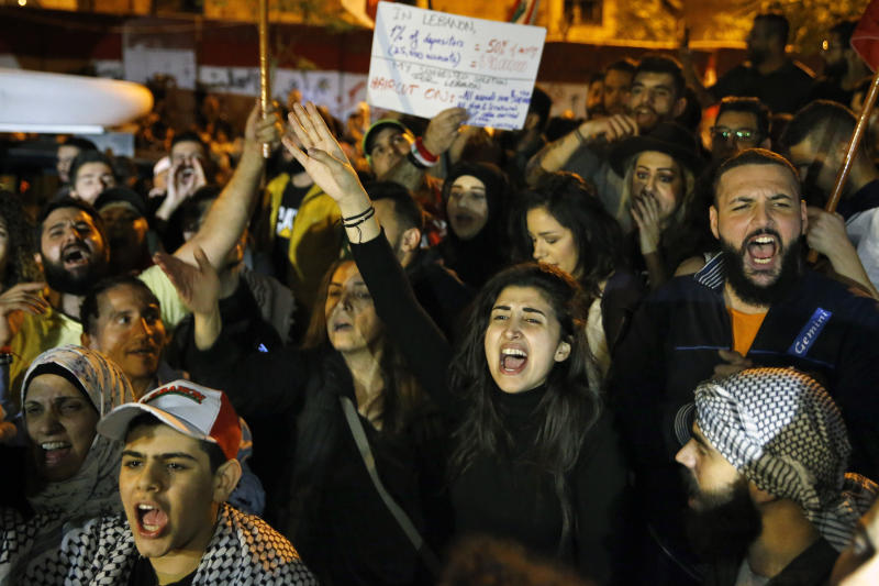 Anti-government protesters chant slogans, during ongoing protests against the Lebanese government, in front of the Central Bank, in Beirut, Lebanon, Thursday, Nov. 28, 2019. Lebanon paid back a Eurobond worth $1.5 billion that was scheduled to mature Thursday, a Finance Ministry official said, pacifying concerns of a first-ever default on its debt amid the worst financial crisis in three decades. (AP Photo/Bilal Hussein)