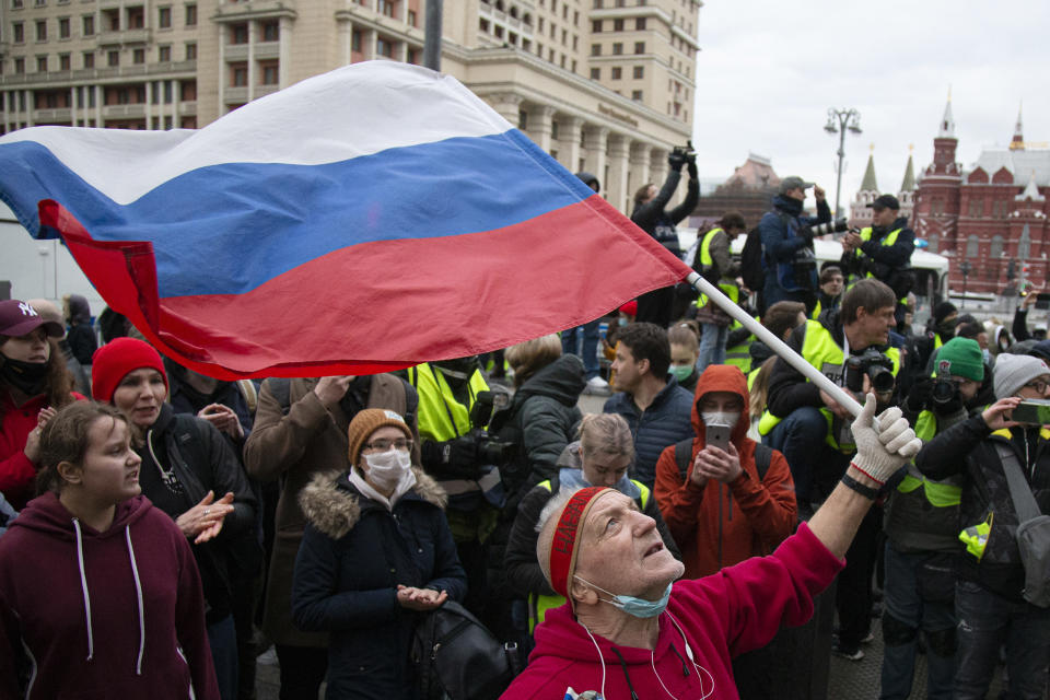 A supporter waves the Russian national flag and shouts slogans during the opposition rally in support of jailed opposition leader Alexei Navalny in the center of Moscow near Red Square, Russia, Wednesday, April 21, 2021. Police across Russia have detained large numbers of people in connection with demonstrations in support of imprisoned opposition leader Alexei Navalny, according to a human rights group. (AP Photo/Alexander Zemlianichenko)