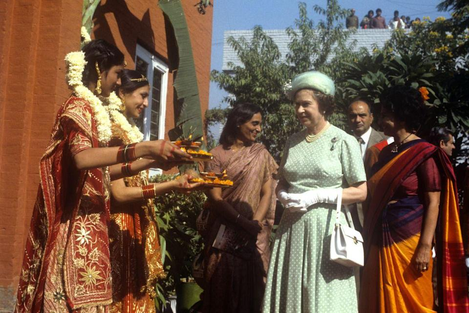 <p>The Queen is offered food by girls in traditional Indian dress at the Mahatma Gandhi memorial at Raj Ghat, Delhi. (PA Archive) </p>