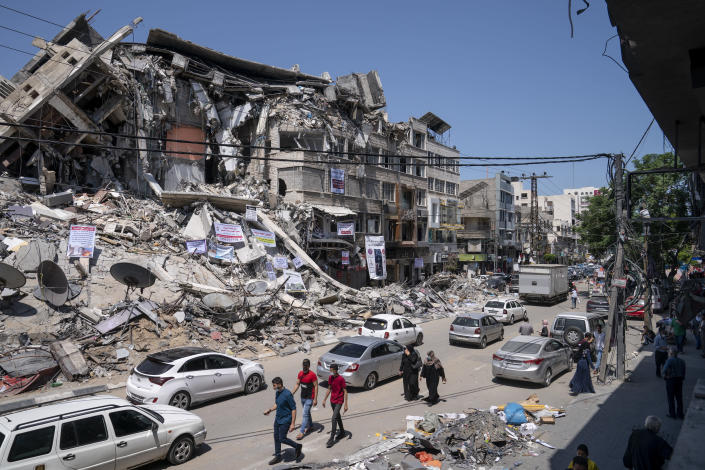 Motorists and pedestrians move past a building destroyed by an air-strike prior to a cease-fire that halted the 11-day war between Gaza's Hamas rulers and Israel, Tuesday, May 25, 2021, in Gaza City, the Gaza Strip. (AP Photo/John Minchillo)