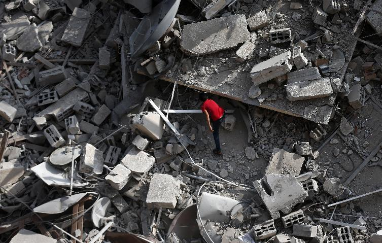 A Palestinian man inspects the rubble of an 12-storey apartment building that collaped the day before after it was hit by missiles during an Israeli air strike in the heart of Gaza City, August 24, 2014 (AFP Photo/Thomas Coex)