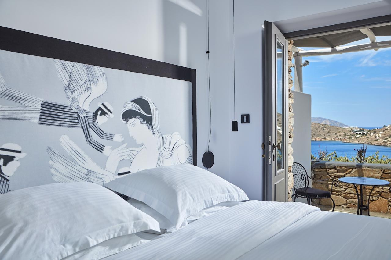 """Though the hotel's hallmark is a red poolside sculpture from Greek artist Kostas Georgiou, common spaces and rooms at <a href=""""https://www.liostasi.gr/"""">this boutique hotel</a>—a member of Small Luxury Hotels of the World—are filled with their own notable <em>objets d'art</em> and handcrafted elements: See the glass baubles, woven baskets, and driftwood furniture here, there, and everywhere. Suites, done in brown, gray, and green by designer Antonis Kalogridis, have black-and-white headboards, tree-trunk tables, and all-marble bathrooms with mirrored doors; all come with private terraces."""