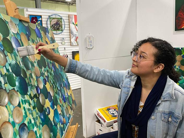 """Charlotte artist Rosa Renteria Jimenez in her studio at Charlotte Art League. This painting is called """"Fragile 1."""""""