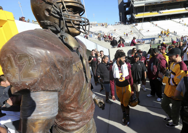 Arizona State senior quarterback Manny Wilkins (5) walks off the field past the Pat Tillman statue for the final time as a player following a 31-28 victory against UCLA during an NCAA college football game, Saturday, Nov. 10, 2018, in Tempe, Ariz. (AP Photo/Ralph Freso)