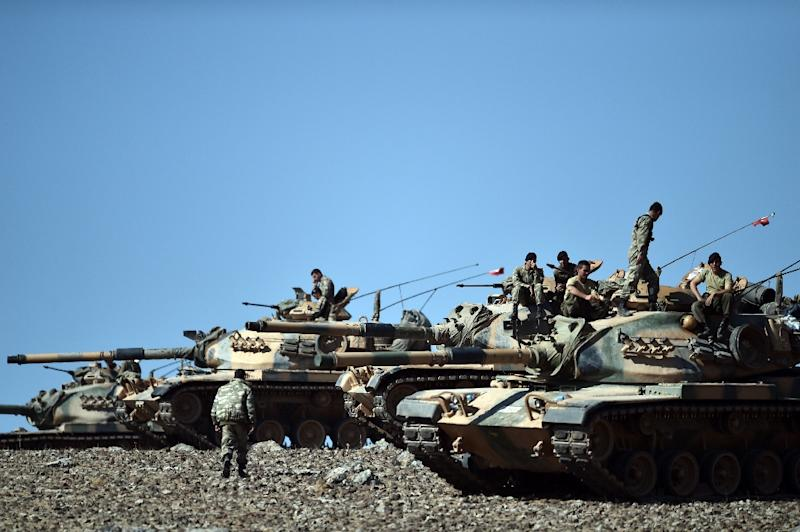 Turkish tanks line up on a hill near the border with Syria in 2014 (AFP Photo/Aris Messinis)