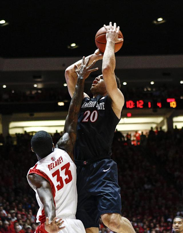 San Diego State's JJ O'Brien (20) shoots over New Mexico's Deshawn Delaney (33) during the first half of an NCAA college basketball game at The Pit in Albuquerque, N.M., Saturday, Feb. 22, 2014. (AP Photo/Juan Antonio Labreche)