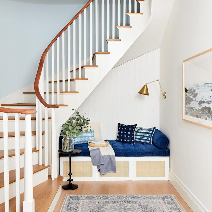 Stylish throw pillows and a gold wall fixture adorn the cozy area under the 2020 Real Simple Home's main staircase.
