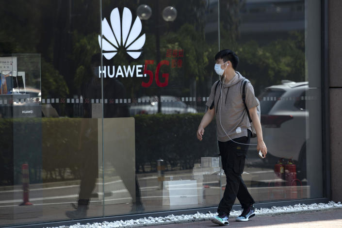 A man wearing a mask to curb the spread of the coronavirus walks past a Huawei store promoting 5G technologies in Beijing on Wednesday, July 15, 2020. China's government accused Britain on Wednesday of colluding with Washington to hurt Chinese companies after tech giant Huawei was blocked from working on a next-generation mobile phone network. (AP Photo/Ng Han Guan)