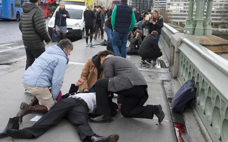 Victims of Wednesday's terror attack receive treatment from passers by on Westminster Bridge - REUTERS
