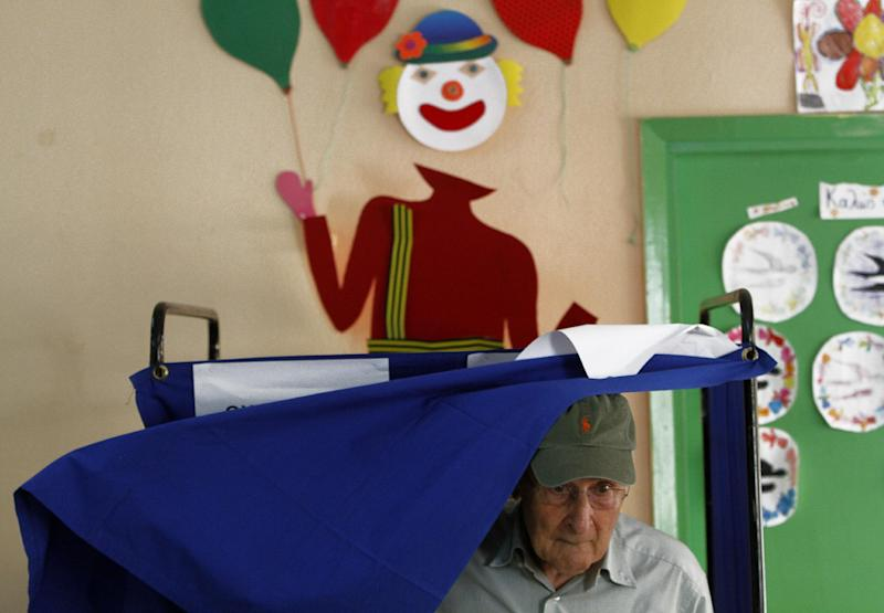 A Greek man leaves the booth after voting during the parliamentary elections in Athens, Sunday, June 17, 2012. Greeks vote Sunday for the second time in six weeks in what may be their country's most critical election in 40-years.(AP Photo/Petros Karadjias)