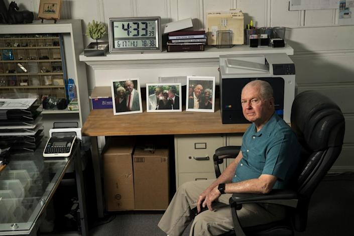 A man sits in an office chair in an office. On his desks are photos of himself and a friend.