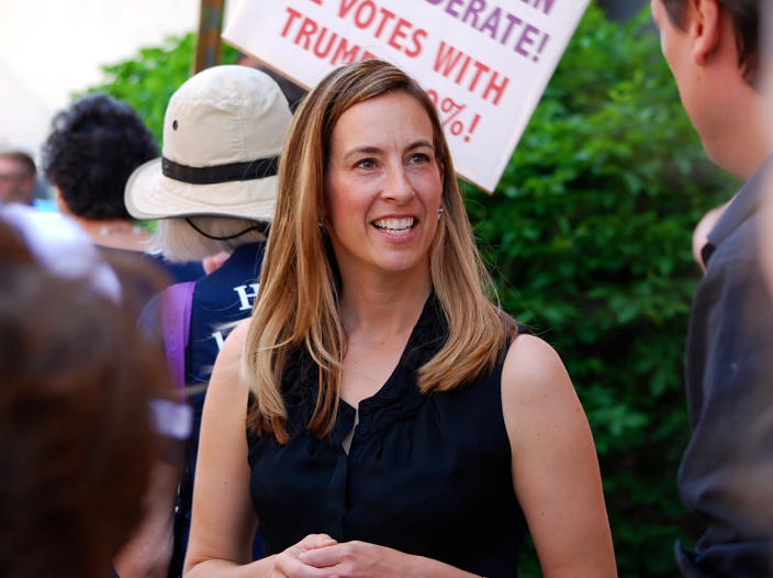 FILE- In this May 19, 2017, file photo, Mikie Sherrill joins protesters with NJ 11th for Change outside of U.S. Rep. Rodney Frelinghuysen's Morristown office. Sherrill, a former Navy helicopter pilot and federal prosecutor, is looking to capture a GOP congressional seat in New Jersey. Sherrill is one of some 200 women who have won their primaries for U.S. House, with 94 of these candidates surviving crowded fields with three or more candidates, according to an analysis of election results. (Justin Zaremba/NJ Advance Media via AP, File)