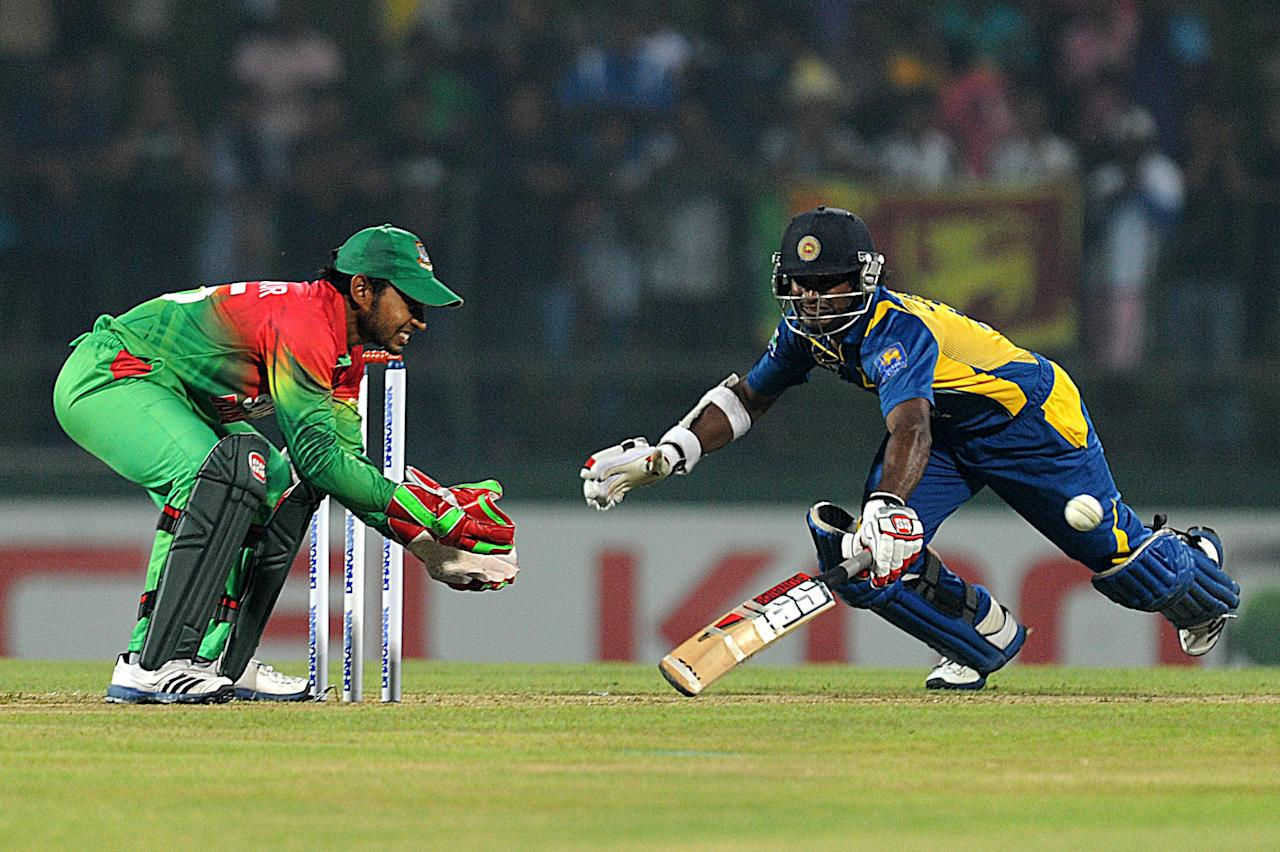 Sri Lankan cricketer Kusal Janith Perera (R) makes a dash for the wicket as Bangladesh captain Mushfiqur Rahim prepares to field during the the Twenty20 International match between Sri Lanka and Bangladesh at The Pallekele International Cricket Stadium in Pallekele on March 31, 2013. AFP PHOTO/ Ishara S. KODIKARA