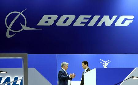 FILE PHOTO: Visitors talk on the Boeing stand during the EBACE at Cointrin Airport in Geneva