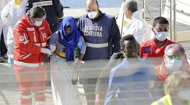 A migrant is helped as she disembarks from a Coast Guard boat in the Sicilian harbour of Palermo. Photo: REUTERS/Guglielmo Mangiapane