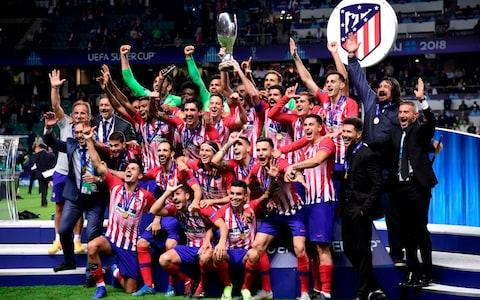 Atletico's players celebrate with the trophy - Credit: GEtty images